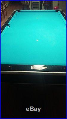 9 foot Brunswick slate pool table with ball return. New bumpers and felt